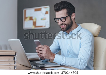 Great news. Handsome young man wearing glasses holding smart phone and looking at it with smile while sitting at his working place - stock photo