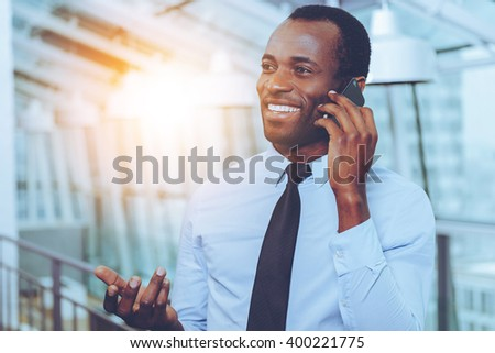 Great news! Happy young African man in shirt and tie talking on the mobile phone and gesturing while standing indoors - stock photo