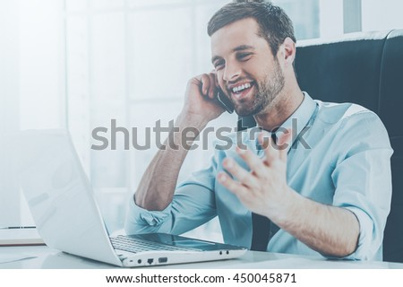 Great news! Happy young man in formalwear looking at computer monitor and talking on the mobile phone while sitting at his working place - stock photo