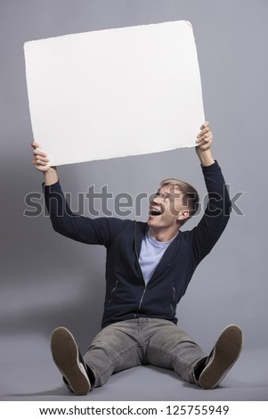 Great news: Joyful young man holding up white empty panel with space for text isolated on grey background. - stock photo