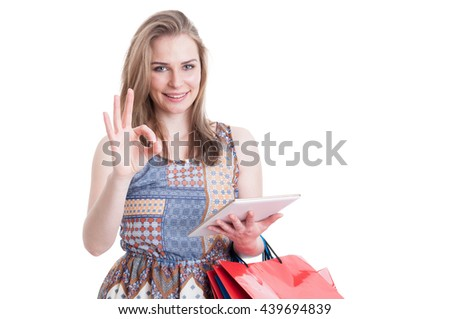 Great online shopping concept with cheerful woman showing ok sign and holding modern tablet and shopping bags isolated on white - stock photo