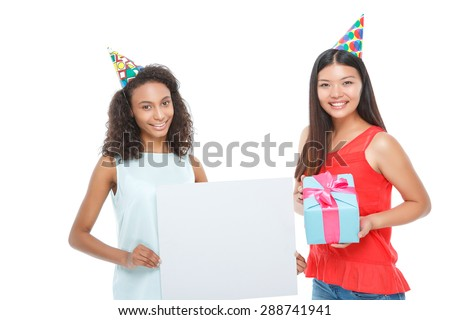 Great party.  Nice smiling girl holding white board with her friend standing beside and keeping present. - stock photo