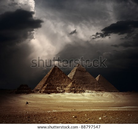 Great pyramids in Giza valley with dark clouds on the background - stock photo