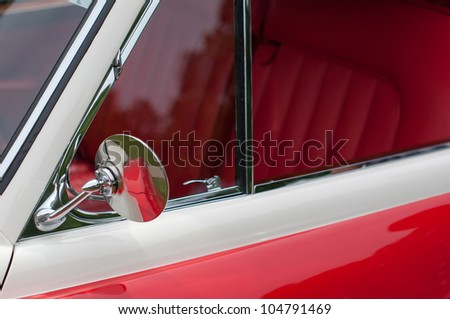 great red oldtimer vintage car detail: mirror and front seat row - stock photo