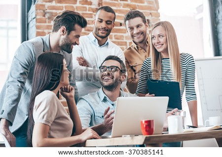 Great result! Group of six young people discuss something with smile while leaning to the table in office - stock photo