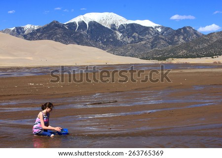 GREAT SAND DUNES NATIONAL PARK, COLORADO - March 22, 2015 - young girl fills bucket with sand and mud - Rocky Mountains in background - stock photo