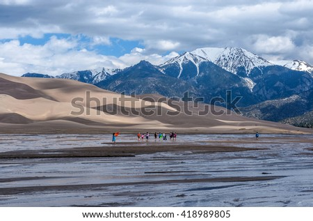Great Sand Dunes National Park & Preserve, Colorado, USA - May 06, 2016: A group kids are playing in Medano Creek at the base of sand dunes and snow-capped peaks as spring clouds passing over. - stock photo
