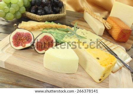 great selection of cheese with fork, grapes and figs - stock photo