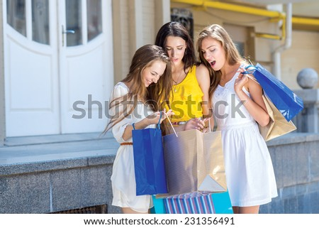 Great shopping choice. Three young and pretty girls are standing with shopping bags. One of them is showing her new just bought dress - stock photo