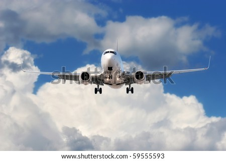 Great shot of a large airplane almost overhead departing or ready to land, shot against bright blue sky and white clouds. - stock photo