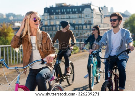 Great time with friends. Beautiful young smiling woman riding bicycle and looking away while her friends riding in the background - stock photo