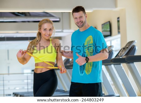 Great training result. Young and pretty woman is measuring her training result. Handsome athlete man is standing next to her and looks forward with smile - stock photo