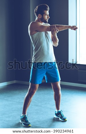 Great warm-up. Full-length of young man in sportswear stretching his arm at gym - stock photo