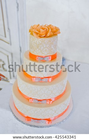 Great wedding cake with orange ribbons - stock photo