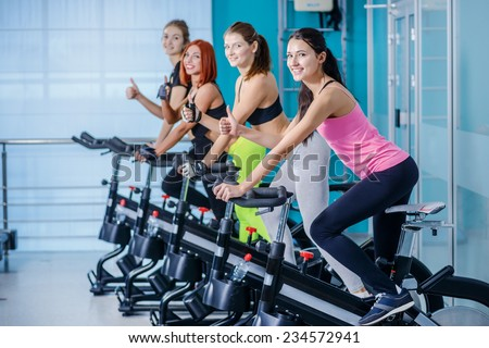 Great workout. Sport women pedaling on the simulator while four friends athletes pedaling on a stationary bike at the gym showing thumb up. - stock photo