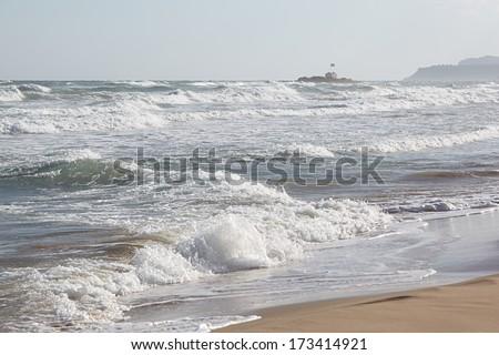 Greece, Crete. Stormy sea on the background of a small chapel in Malia - stock photo