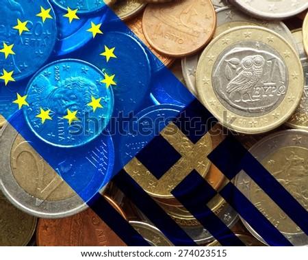 Greece crisis - European flag and flag of Greece over a bunch of Greek euro coins - stock photo