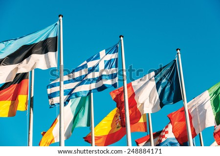 Greece flag waving in front of European Parliament, next to Estonia, France, Italian, Spain, Germany flags on a clear blue sky - stock photo