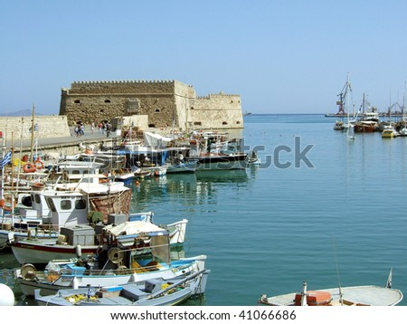 Greece Heraklion port with boats and old tower - stock photo