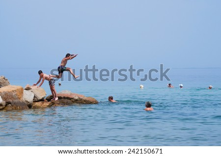 GREECE - JUNE 26: Boys jumps from a rocks into the sea on a sunny day on June 26,2014 on the beach in Nikiti, Sithonia peninsula, Greece. - stock photo