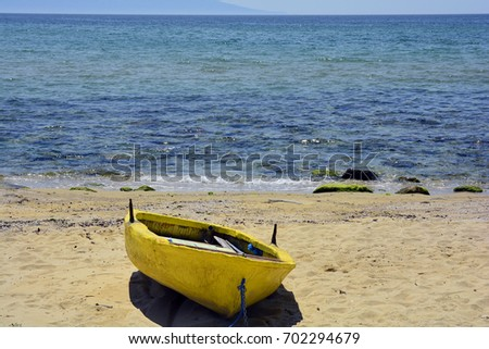 Greece, Kavala, yellow rowing boat on beach of Aegean sea