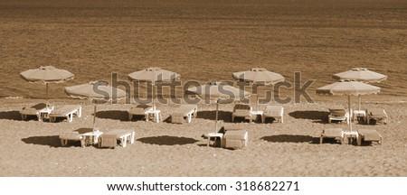 Greece. Kos island. Kefalos beach. Chairs and umbrellas on the beach. In Sepia toned. Retro style  - stock photo