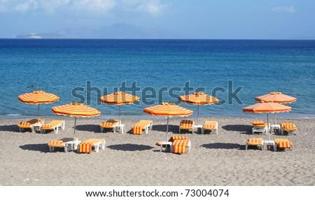 Greece. Kos island. Kefalos beach. Orange chairs and umbrellas on the beach - stock photo