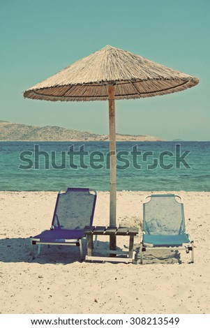 Greece. Kos island. Tigaki beach.Two chairs and umbrella on the white sand beach. In instagram style filtered - stock photo