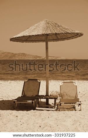 Greece. Kos island. Tigaki beach.Two chairs and umbrella on the white sand beach. In Sepia toned. Retro style - stock photo