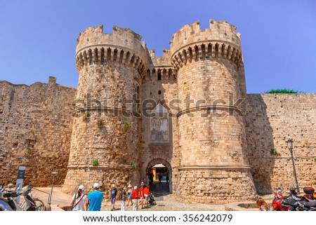 GREECE, RHODES - JUNE 11, 2015: Tourists visiting the Old Town at the Marine Gate (also Sea Gate) at the old city of Rhodes, Greece. - stock photo