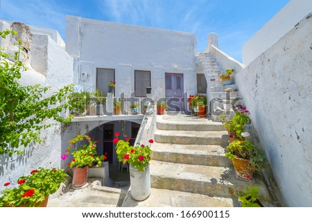 Greece Santorini island in cyclades colorful view of whitewashed houses among small walk paths that cross the island with wooden door frames and flower pots - stock photo