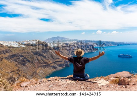 Greece Santorini island in Cyclades, tourist traveler enjoyng the amazing view with awe with hands open - stock photo