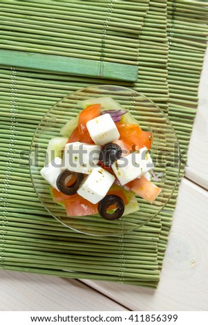 Greece style salad in glass bowl on textile and wood mat - stock photo