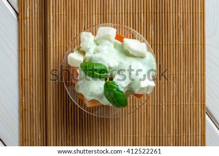 Greece style salad in green sauce in glass bowl on textile - stock photo