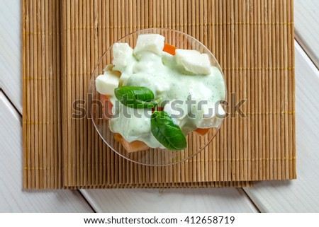 Greece style salad in green sauce in glass bowl on wood - stock photo