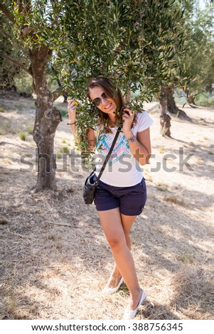 Greece. The island of Zakynthos. Portrait of a young woman in sunglasses standing next to a tree around the olive green leaves