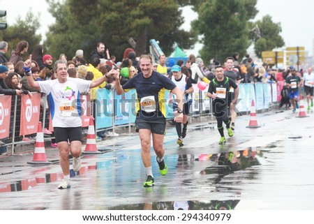 GREECE, Thessaloniki April 5, 2015: Runners in the 10th International Alexander the Great Marathon (from Pella to Thessaloniki) near the finish line of the 42 kilometers run at the White Tower square. - stock photo