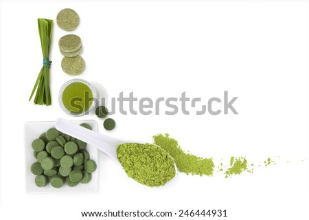 Greed superfood. Spirulina, chlorella and wheat grass ground powder, effervescent tablets, grass blades isolated on white background, top view. Detox and healthy living.  - stock photo