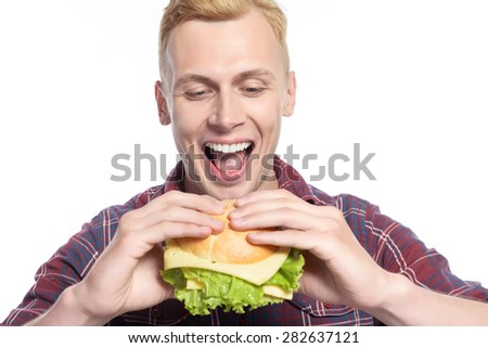 Greedily eating. Attractive young man going to eat sandwich on isolated white background - stock photo