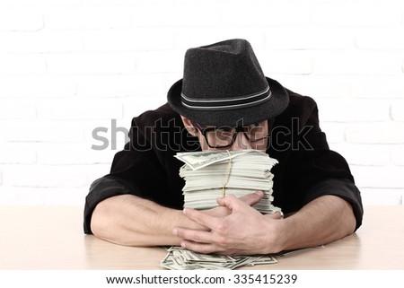 Greediness. emotional man in glasses holding bundles of money  Greed - stock photo