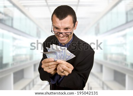 Greedy business man with money at the office - stock photo