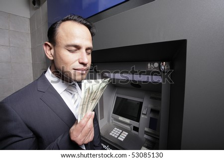 Greedy businessman smelling his money