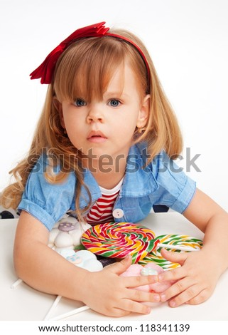 Greedy  girl with pile of sweets laying on the table and with troubled expression on the face - stock photo