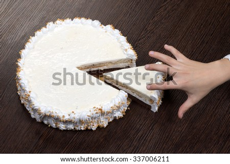 Greedy hand grabs a piece of a large white cake with a blank top - stock photo