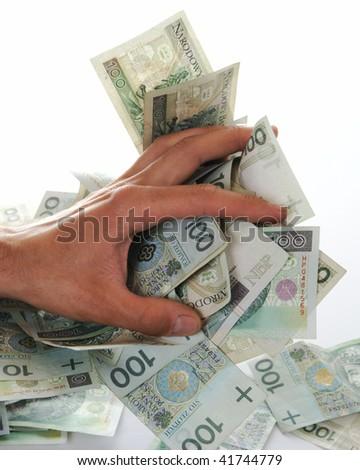 Greedy hand grabs money lot of polish banknotes - stock photo