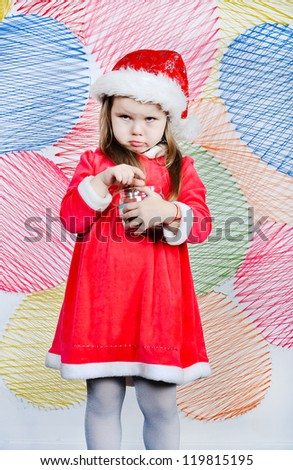 Greedy little girl in Santa dress up with jar full of sweets on the colorful background - stock photo