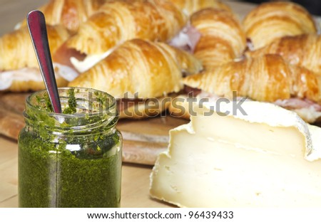 greedy snack preparation with croissant, cheese and garden rocket sauce