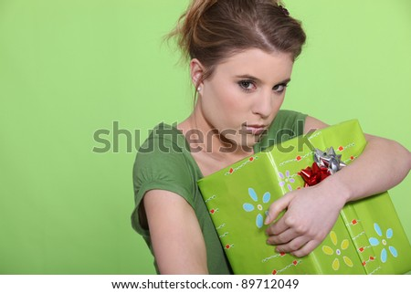 Greedy woman hugging her present all to herself - stock photo