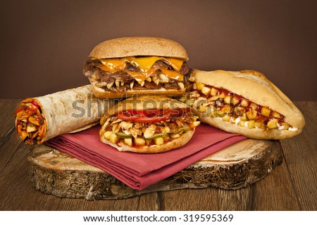 Greek and Turkish gyros stuffed sandwich with roasted meat salad onions fried potatoes and tzatziki saucer olled into a pita on a plate Patso with chicken doner kebab shawarma and sandwich - stock photo
