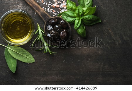 Greek black olives, fresh green sage, rosemary, basil herbs, salt and oil on dark rustic wooden background.  Top view, copy space - stock photo